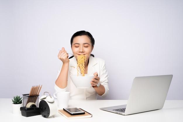 사무실에서 초과 근무 후 인스턴트 국수를 먹는 아시아 여성. 일을 마친 후 국수에 만족하는 사업가입니다.