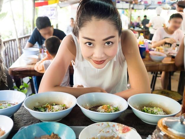 タイの地元のレストランでアジアの女性が食べるヌードル。
