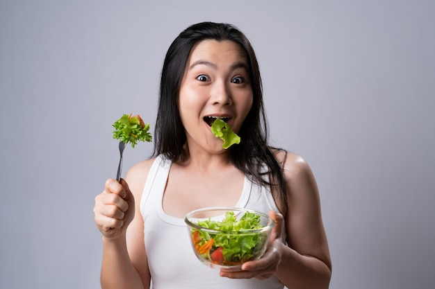 Asian woman eating salad for diet isolated over white wall. healthy lifestyle with clean food concept.