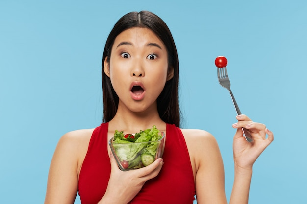 Asian woman eating salad
