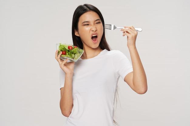 Asian woman eating salad
