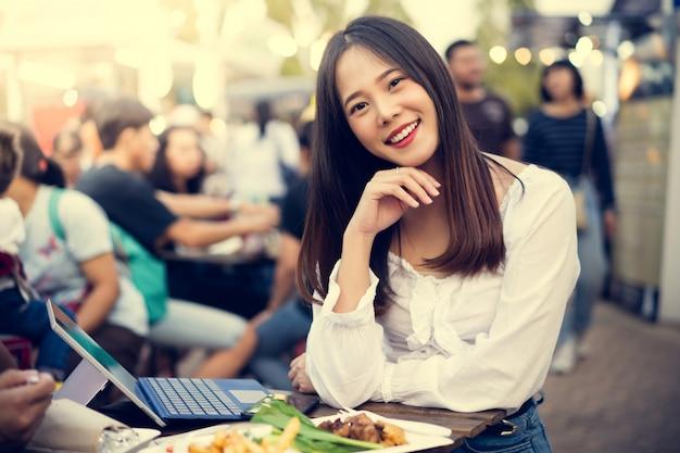 Азиатская женщина ест уличную еду, и она работает в своей компании