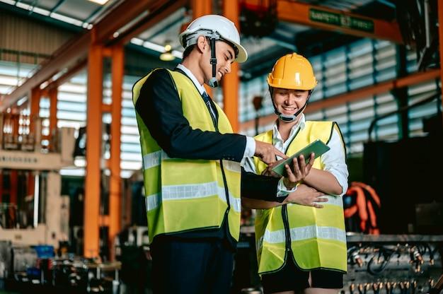 ヘルメットをかぶって、機械エリアに立っているチェックリストを保持しているアジアの女性エンジニア業界