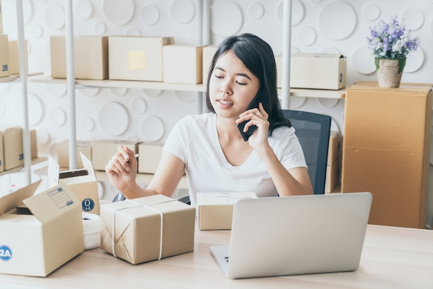 Asian woman enjoy herself while using internet on laptop and phone in office