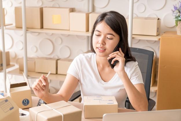 Азиатская женщина наслаждается пока использующ интернет на компьтер-книжке и телефоне в офисе