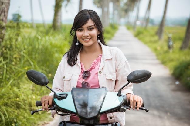アジアの女性は熱帯の田舎道で彼女のバイクに乗って楽しむ