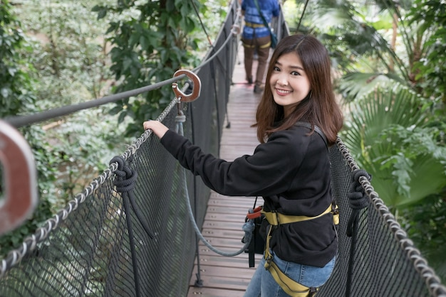 Asian woman enjoy travelling on hanging bridge in the forest, doi tung