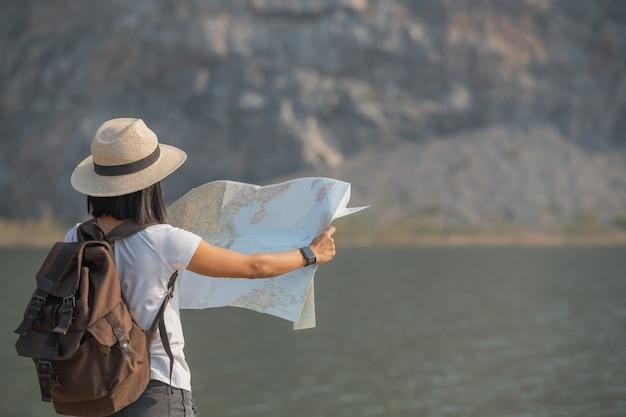 Asian woman enjoying beauty of nature looking at mountain lake