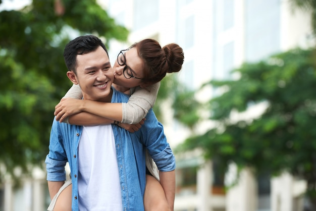 Asian woman enjoying piggyback ride on boyfriend