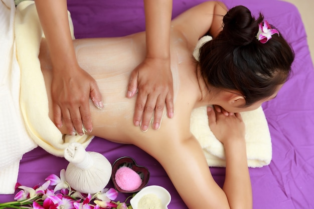 Asian woman enjoying a salt scrub massage at spa.