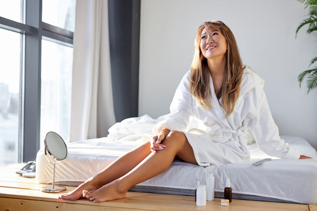 부드러운 다리 피부를 즐기는 아시아 여자, 화장품 사용 후 다리를 만지고, 목욕 가운에 침대에 앉아 웃고