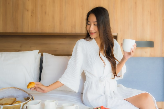 Asian woman enjoying with breakfast on bed