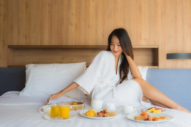 アジアの女性がベッドで朝食を楽しんで