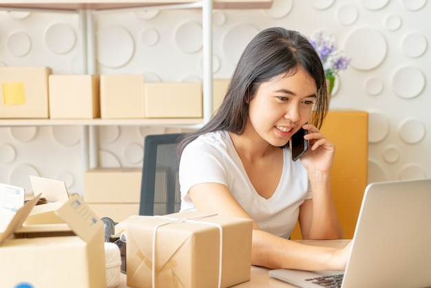 Asian woman enjoys herself while using internet on laptop and phone in office