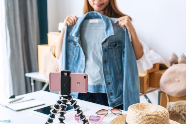カメラを話すアジアの女性起業家は、自宅のソーシャルネットワークに住んでいます。オンライン販売のコンセプト。