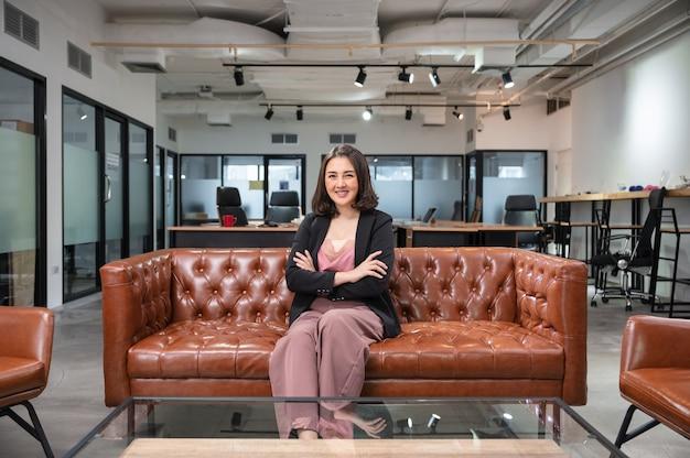 アジアの女性起業家は、コワーキングスペースのヴィンテージソファに座って笑顔に自信を持っています