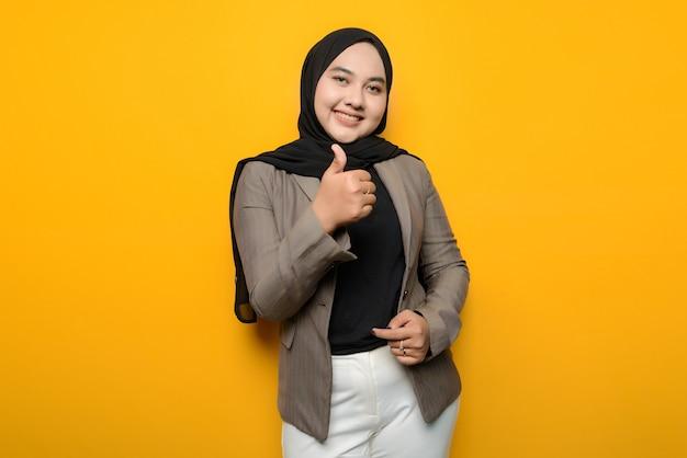 黄色の背景に興奮しているアジアの女性