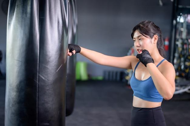 フィットネスジムでのアジアの女性の運動とライフスタイル。スポーティな女性のトレーニングとトレーナーとのボクシング。ボディービルのための健康と健康。