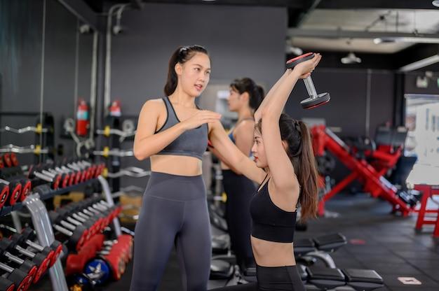 フィットネスジムでのアジアの女性の運動とライフスタイル。トレーナーとダンベルウェイトでスポーティな女性のトレーニング。ボディービルのための健康と健康。