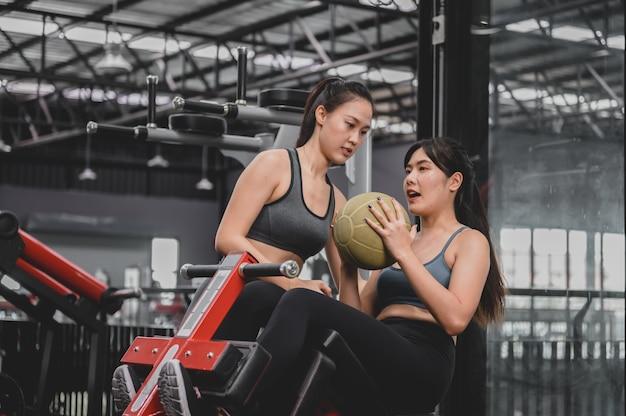 フィットネスジムでのアジアの女性の運動とライフスタイル。トレーナーとのスポーティな女性のトレーニング。ボディービルのための健康と健康。