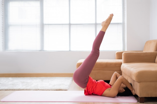 Азиатская женщина упражнения дома. абдоминальные упражнения