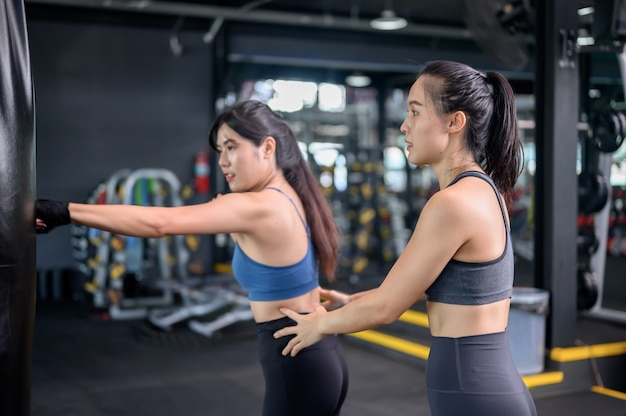 Asian woman exercise and lifestyle at fitness gym. sporty woman workout and boxing with trainer. wellness and healthy for bodybuilding.