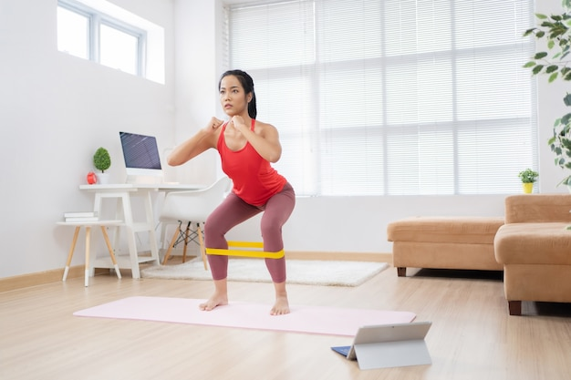 Азиатская женщина работает дома на коврике для йоги.