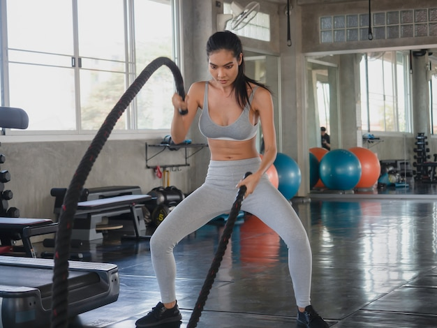 Asian woman exercising with battle ropes at gym