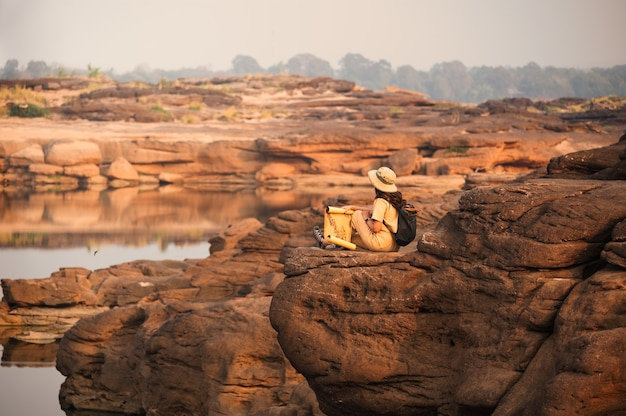 태국의 sam phan bok 그랜드 캐년에서 종이지도를보고 바위 절벽에 앉아 아시아 여자 탐험가