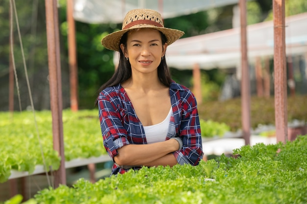 행복과 야채 수경 농장에서 일하는 아시아 여성 농부. 그린 하우스 농장에서 미소로 그린 샐러드 야채의 품질을 확인하는 여자 농부의 초상화.