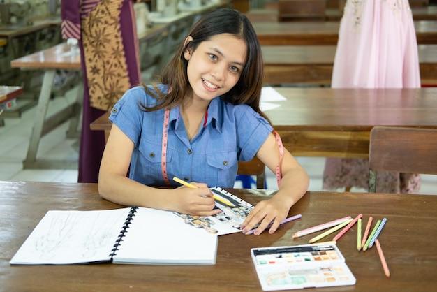 描くときに笑っているアジアの女性ファッションデザイナーは、衣料品製造室で文房具を使用してドレススケッチを描く