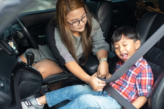 Asian woman fastening child with safety seat belt in car.