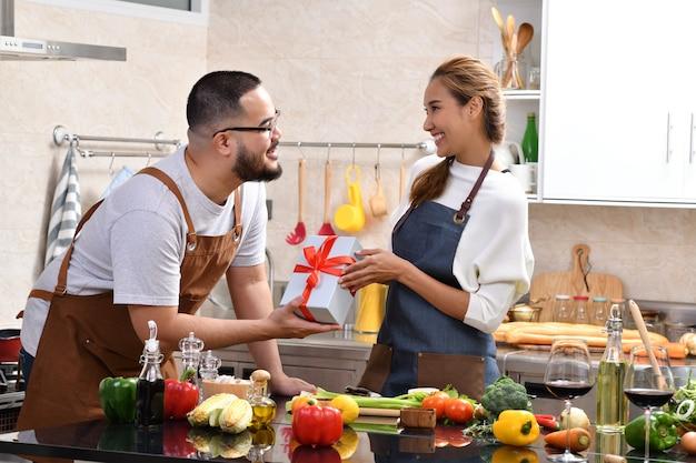 アジアの女性は、キッチンで料理をして一緒に健康食品を作っているときにボーイフレンドからの贈り物に驚いたときに幸せを感じています