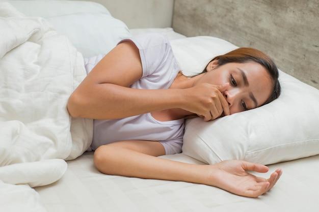 집에서 침대에서 자고 아픈 문제 발열과 기침을 느끼는 아시아 여성