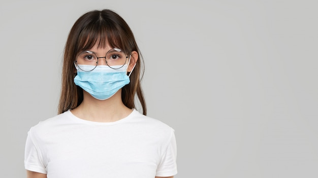 Asian woman feeling unwell and wearing face protective mask on grey studio background. copy space for text. the first defense against the epidemic of flu and coronavirus