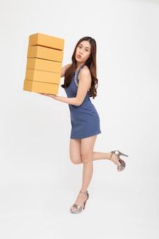흰색 배경에 격리된 소포 상자를 들고 와우 느낌을 받는 아시아 여성