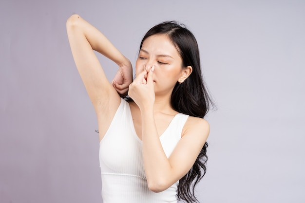 Asian woman feels uncomfortable because of armpit odor