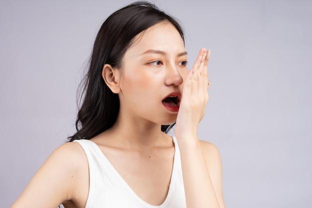 Азиатская женщина чувствует себя некомфортно из-за неприятного запаха изо рта