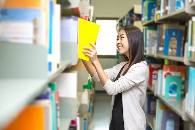 Asian woman find a book with smiling at library