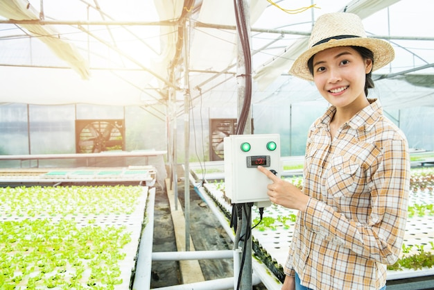 Asian woman finger press on temperature control machine in greenhouse hydroponic farm