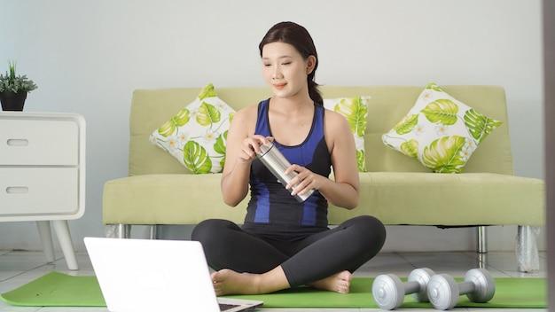 アジアの女性は彼女のラップトップ画面を見て家で休んでヨガを終えた