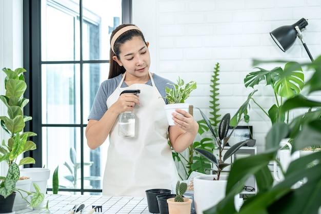 Азиатская женщина-садовник держит горшок с растением и ухаживает за растениями, распыляя воду удобрения на растения в комнате дома, стоя для хобби, концепция домашнего сада