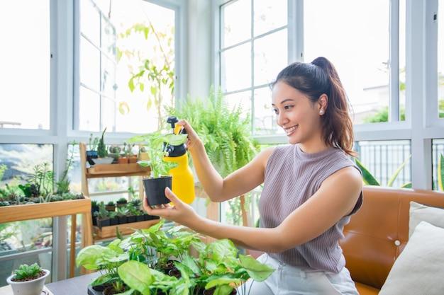 アジアの女性庭師自宅のリラックスした一日のために庭の植物に水を噴霧します。