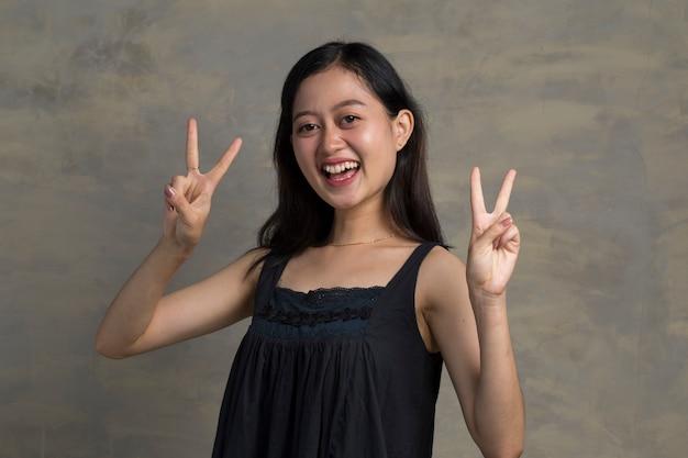 Азиатская женщина дает победу мира, два знака жест