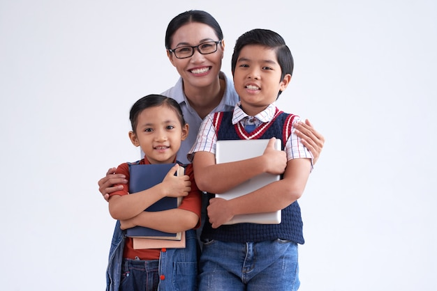 Asian woman in glasses hugging two young schoolchildren