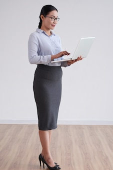 Asian woman in glasses and smart clothes standing in studio and using laptop