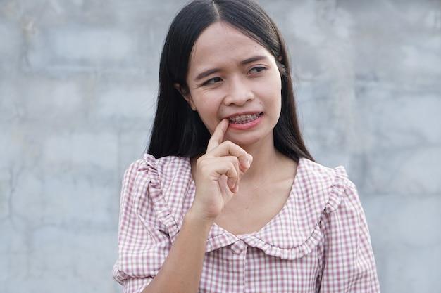 アジアの女性は彼女の手で彼女の歯に食べ物をかじる