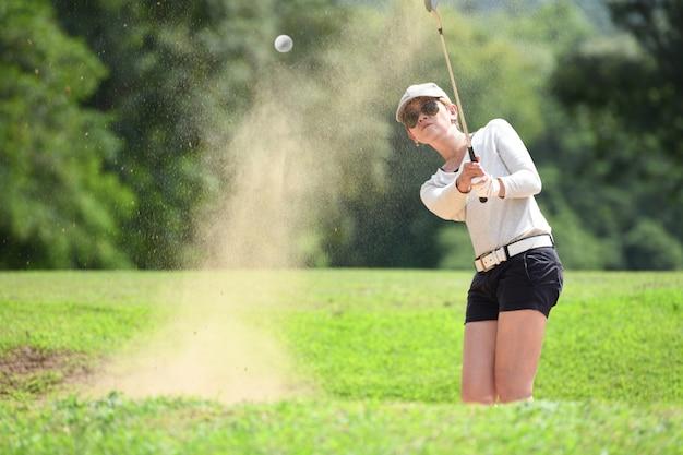 Азиатский гольфист, ударяя выстрел бункера