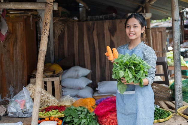 Asian woman greengrocer smiles while holding carrot and spinach at a vegetable stall in a traditional market