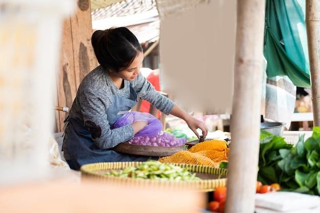 アジアの女性八百屋は、野菜スタンドでそれらを計量するために袋から玉ねぎを取ります